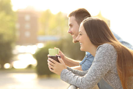 Happy couple enjoying breakfast and looking away in a balcony with an urban background with a warm light at sunset Stock Photo