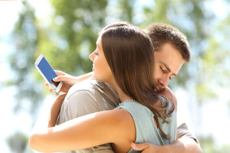 Engaño de la novia de mensajes de texto en el teléfono y abrazando a su novio inocente Foto de archivo - 68856393