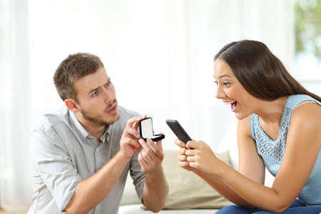 Amazed woman using a smart phone ignoring a marriage proposal of her worried boyfriend at home
