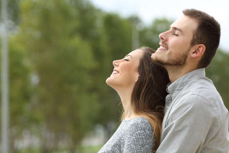Side view portrait of a happy couple breathing together fresh air in a park with green trees in the background