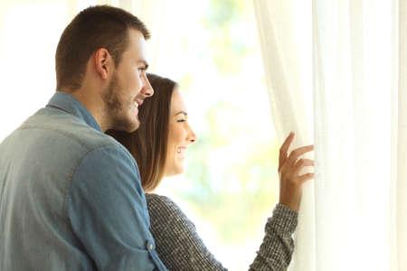 다정한 결혼 생활을 시작하는 커튼과 따뜻한 빛으로 새로운 아름다운 하루에 창문을 통해 밖을보고 스톡 콘텐츠