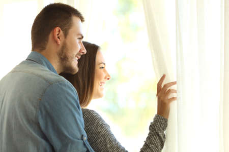 Affectionate marriage opening curtains and looking outside through a window in a new beautiful day with a warm light Stock Photo
