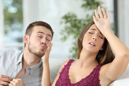 Vrouw die hoofdpijn beweert om seks met haar indringende vriendje te vermijden Stockfoto
