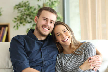 Front view portrait of a happy couple posing and looking at camera sitting on a couch in the living room at home