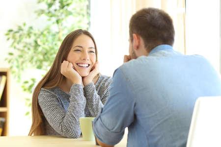 ragazza innamorata: Ragazza romantica innamorarsi in un primo appuntamento seduto in un tavolo nel soggiorno di casa