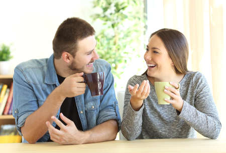 Front view of a casual couple talking looking each other during breakfast in a table of the living room at home Фото со стока