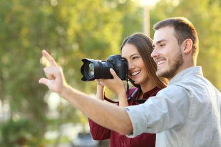 Fotógrafo aprendizaje en un curso de fotografía al aire libre escuchar la explicación del maestro Foto de archivo - 69027680