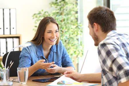 Feliz empresarios tener una conversación de negocios en un escritorio en la oficina Foto de archivo