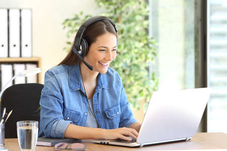 Freelance operator working in telemarketing on line with headsets and a laptop in a desktop at office Foto de archivo