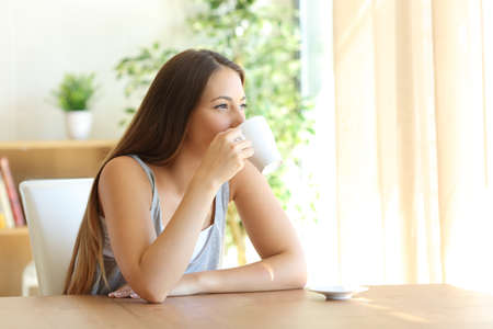 Retrato de una niña sentada en un café de consumición de la silla y mirando hacia afuera a través de una ventana en el país con una cálida luz natural