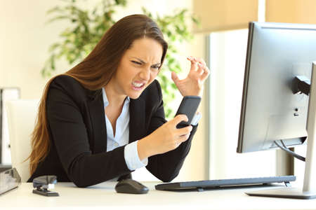Furious businesswoman wearing suit working on line using a smart phone in a desk at office