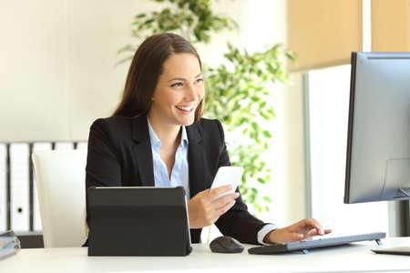 複数のデバイスとラインで作業、オフィスでデスクトップ コンピューターを見て幸せの実業家 写真素材
