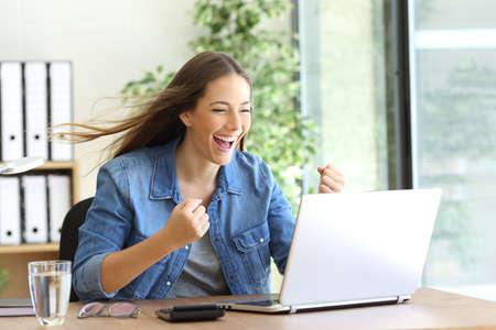 ganancias: empresario emocionada que trabaja en línea con un ordenador portátil en la oficina y el pelo movido por el viento