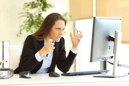 Woedend zakenvrouw draagt pak met behulp van een desktop computer op de lijn naast een raam op het kantoor van Stockfoto