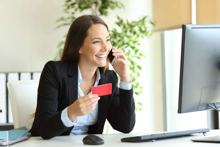Feliz empresaria trabajando comprando en línea con tarjeta de crédito y llamando al servicio al cliente en la oficina