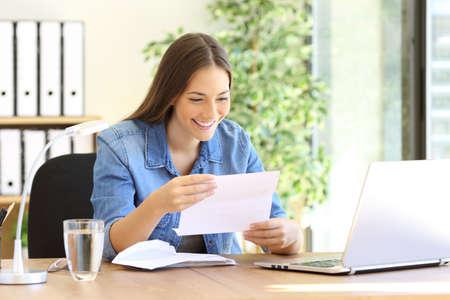 Szczęśliwy przedsiębiorca kobieta czyta dobre wieści w liście na biurku w biurze