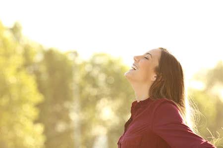 Zijaanzicht van een gelukkige vrouw inademen van frisse lucht buiten met een groene achtergrond en een warm licht Stockfoto