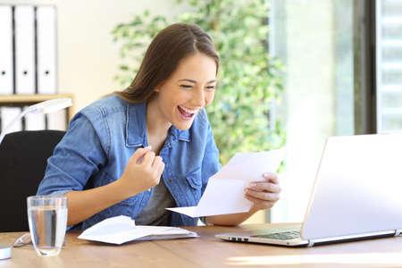 Opgewekte toevallige ondernemer meisje lezing goed nieuws in een brief in een Desktop op kantoor