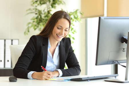 Empresaria lleva el juego que trabaja notas a mano en un escritorio en la oficina