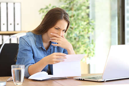 Worried entrepreneur girl working at office reading bad news in a letter on a desktop