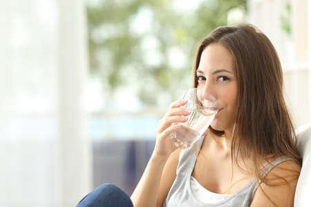 Vrouw drinkwater in huis en op zoek naar jou zittend op een bank in de woonkamer thuis Stockfoto