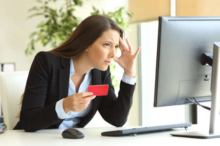 Worried businesswoman wearing suit having problems buying on line with credit card in a desktop at office Zdjęcie Seryjne