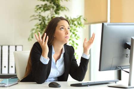 Zmartwiony bizneswoman pracuje online i ono modli się patrzeć above przy biurem Zdjęcie Seryjne