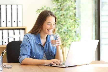 オフィスでラップトップと飲料水、行で働いて幸せな起業家