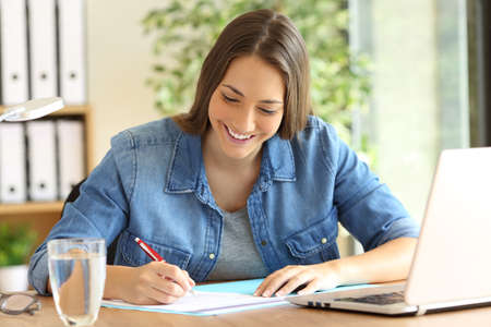 Happy freelance signing or filling form in a desktop at office Stock Photo