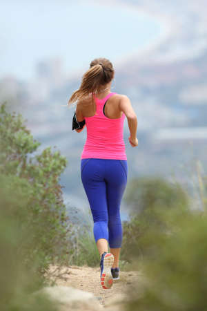 run way: Rear view of a runner wearing colorful sportswear running in the country towards the city