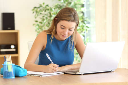 Student studying writing notes in a notebook in a table at home