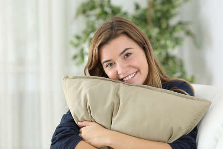 self assurance: Happy teen girl posing looking at you sitting on a couch in the living room at home Stock Photo