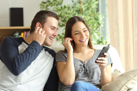 music lyrics: Happy couple listening music and sharing earphones sitting on a sofa in the living room at home