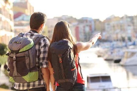 Achtermening van een paar toeristen die in een reisbestemming bezienswaardigheden bezoeken met een haven met kleurrijke gebouwen op de achtergrond Stockfoto