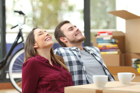 Happy couple sitting on the floor of the living room relaxing together while moving house with a window in the background