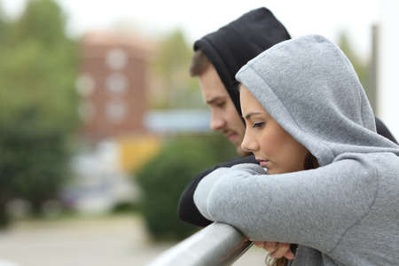 Side view of a sad couple of teens looking down after break up in a balcony of a house with an urban background Stock Photo