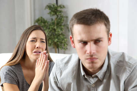 Wife asking for forgiveness to her ex husband after conflict sitting on a couch in the living room of a house Standard-Bild