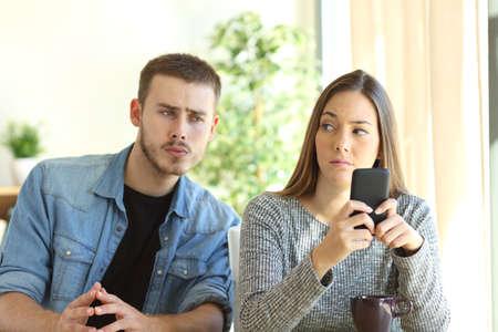novio celoso espiar a su novia mirando a su teléfono mientras ella está buscando le molesta Foto de archivo