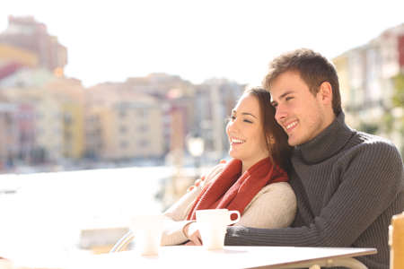romantic man: Couple relaxing sitting in an hotel terrace on holidays with a port in the background in a sunny day of winter