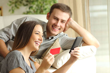cellular: Happy couple buying online with credit card and smart phone on a sofa at home