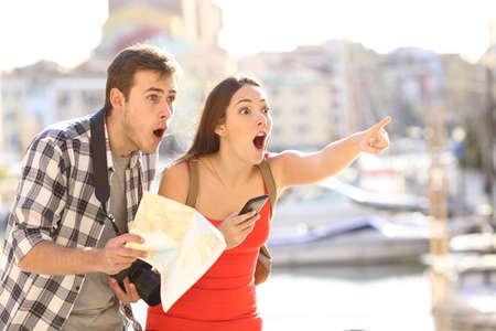 백그라운드에서 마을의 항구와 휴가 여행에서 위치를 찾는 관광객의 놀라 울 된 커플