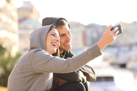 Couple of teens taking a selfie with a smart phone outdoors on holidays with a port in the background