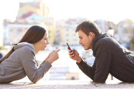 Zijaanzicht van een paar tieners liggend op de vloer van een straat en geobsedeerd door iedereen met zijn slimme telefoon en het negeren van elkaar Stockfoto