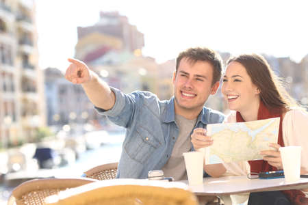 indicating: Couple of tourists searching location siting in an hotel terrace during a summer travel with a port in the background