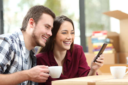 Affectionate couple relaxing and using a smart phone sitting on the floor indoors while moving apartment with carton boxes in the background