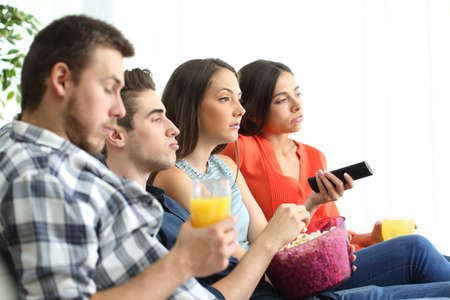 dislike: Side view of bored group of four friends watching a bad tv program sitting on a sofa in the livingroom of an apartment Stock Photo
