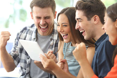 家のインテリアでタブレットからのラインのメディア コンテンツを表示する 4 人の友人の興奮しているグループ