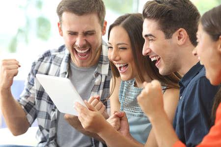 Opgewonden groep van vier vrienden het bekijken van media-inhoud op de lijn van een tablet in een huis interieur