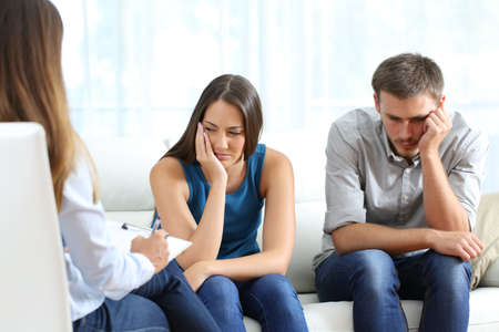 incompatible: Sad couple listening to a marriage counselor during a therapy sitting on a sofa at home