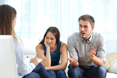 incompatible: Angry husband and sad wife talking with a marriage counselor before breaking up sitting on a sofa at home Stock Photo
